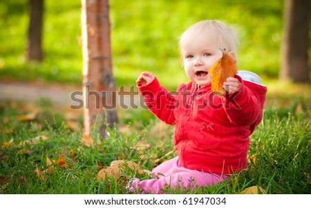 young adorable cheerful baby sit in park on green grass play with leaves - stock photo