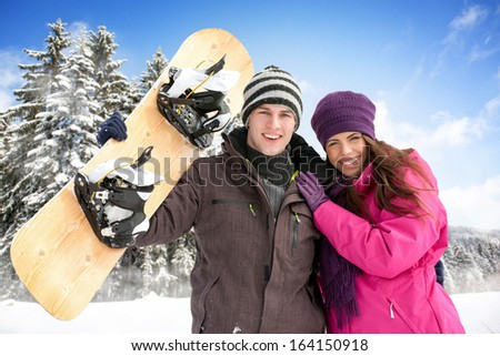 Young adorable couple enjoying in wintertime with snowboard