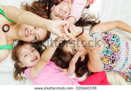 Young adorable hispanic girls and mothers lying down with heads touching and bodies spread out different directions closeup. - stock photo