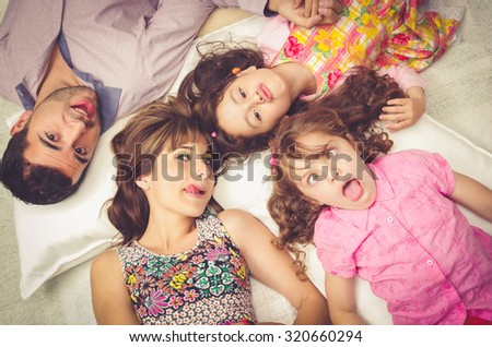 Young adorable hispanic sisters and parents lying down with heads touching and bodies spread out different directions closeup.