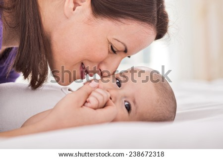 Young adorable mother cuddling her gentle baby - stock photo