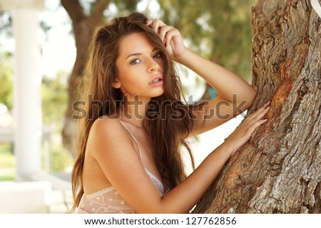 young adorable woman closeup portrait near tree
