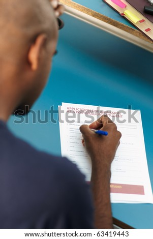 young adult african-american college student filling application form for master degree in library. Vertical shape, rear view, selective focus, head and shoulders - stock photo