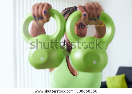 Young adult african american woman in sports clothing at home, doing domestic fitness and training shoulders with weight - stock photo