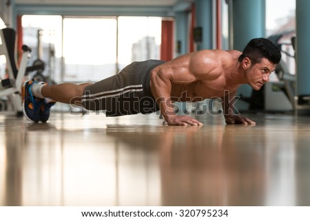 Young Adult Athlete Doing Push Ups As Part Of Bodybuilding Training - stock photo