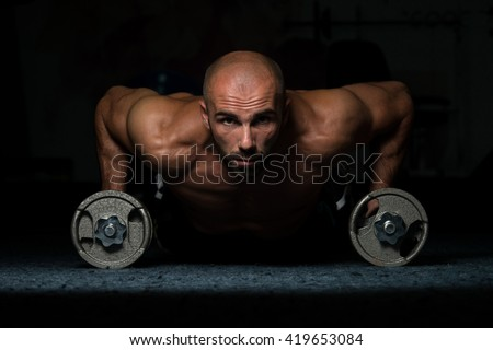 Young Adult Athlete Doing Push Ups With Dumbbells As Part Of Bodybuilding Training In A Dark Room - stock photo