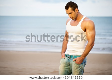 Young adult athlete on beach - stock photo
