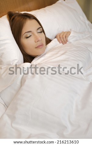 Young adult attractive and sensuality beautiful brunette woman in white bathrobe on the bed - stock photo
