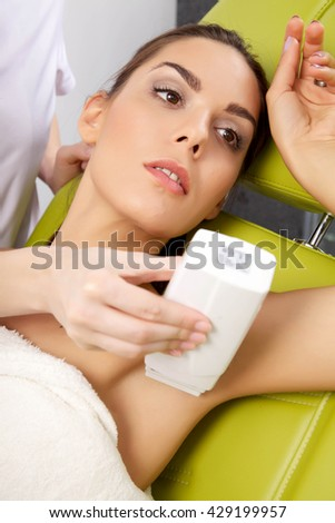 Young adult attractive pretty beauty brunette woman receiving laser therapy. Spa studio shot