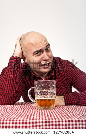 Young adult bald man drinks beer from a jug
