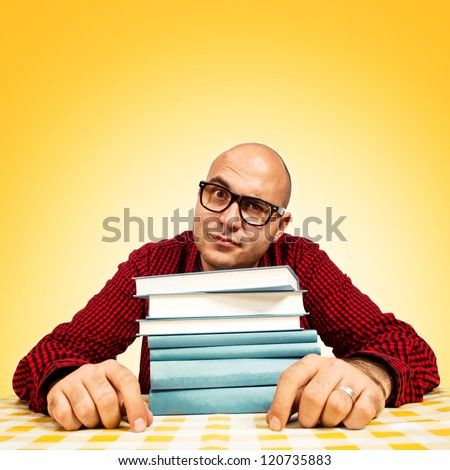 Young adult bald student with few books sitting at the table.