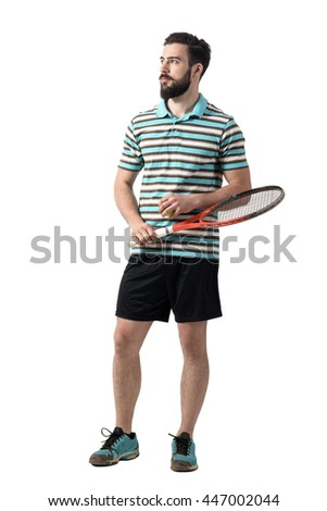 Young adult bearded tennis player holding ball and racket looking away. Full body length portrait isolated over white studio background. - stock photo