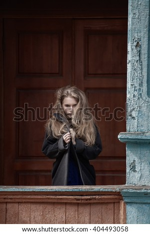Young adult beautiful blond woman in a coat on a background of an old wooden house.