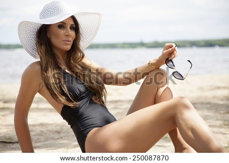 Young adult beautiful sensuality sexy and attractive brunette pretty woman in black swimwear dress and white hat and sunglasses on the sunny beach in summertime