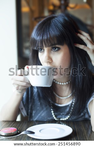 Young adult beautiful woman in the cafe - stock photo
