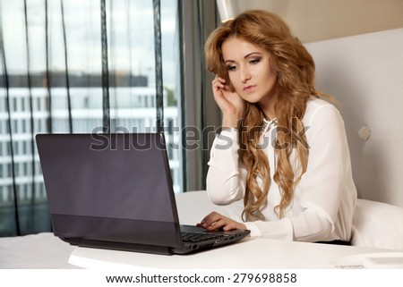 Young adult beauty attractive sexy and sensuality happy pretty blonde businesswoman using laptop while lying on bed in hotel room - stock photo