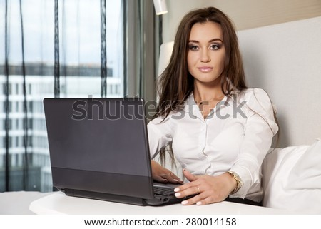 Young adult beauty attractive sexy and sensuality happy pretty brunette businesswoman using laptop while lying on bed in hotel room - stock photo