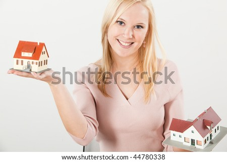 young adult blond woman balancing two houses on with hands