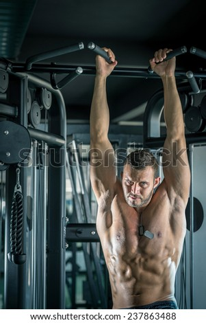 Young adult bodybuilder doing pull ups in gym. - stock photo