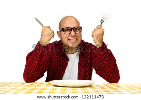 Young adult bold man sitting at the dinner table with fork and knife raised.