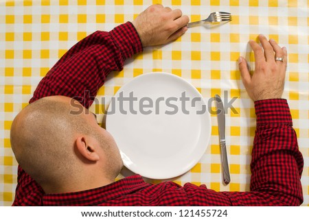 Young adult bold man sleeping at the dinner table with fork and knife in his hands