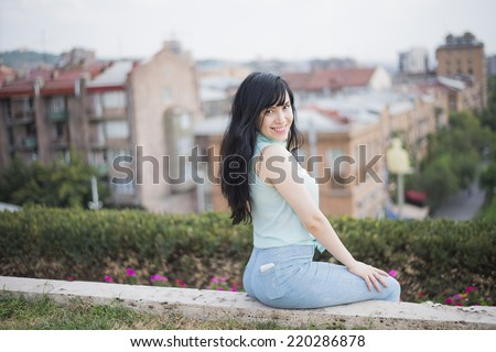 Young adult brunette girl  in casual clothes, sit on edge of terrace, dressed in blue shirt and jeans , Cute woman with long hair looking at camera on big city , flowers sky and bush background  - stock photo