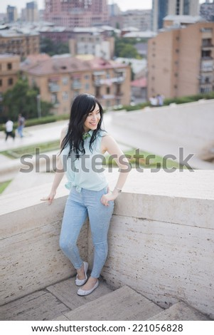 Young adult brunette girl in casual clothes, stand on edge of terrace, dressed in blue shirt and jeans , Cute woman with long hair looking at far on big city , flowers sky and bush background - stock photo