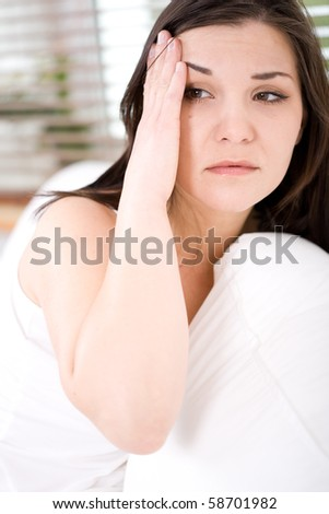 young adult brunette woman feeling pain in bed - stock photo