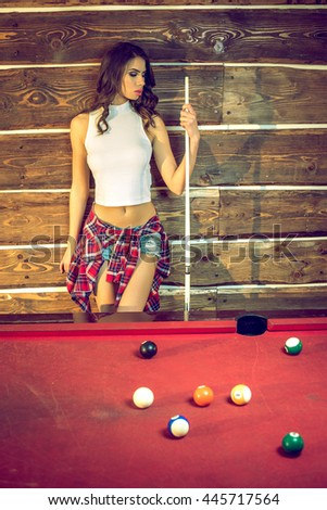 Young adult brunette woman posing in billiard club with pool game equipment: stick, triangle, cues, etc. - stock photo