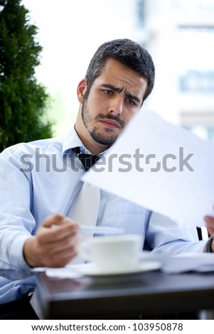 young adult businessman examining documents outdoor