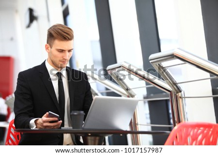 Young adult businessman using laptop in airport lounge