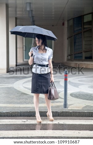 young adult businesswoman on the street under the rain