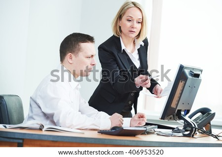 Young adult businesswoman with male colleague on background