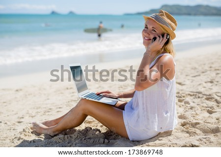 Young adult caucasian blond business woman on vacation using laptop computer PC and talking on cellphone on a tropical beach
