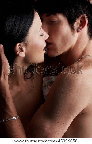 Young adult Caucasian couple in passionate embrace and kissing each other during sexual foreplay