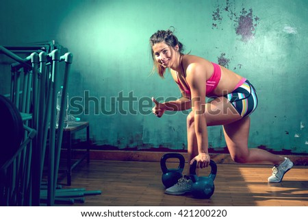Young adult caucasian girl doing lunge exercise indoor with kettlebell. - stock photo