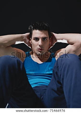 young adult caucasian male in blue sportswear exercising abdominals on black background, looking at camera. Vertical shape, front view, copy space - stock photo