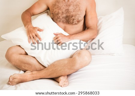 Young adult Caucasian man without clothing in a bed with white pillow