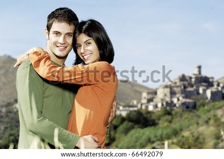 young adult couple embracing in the countryside