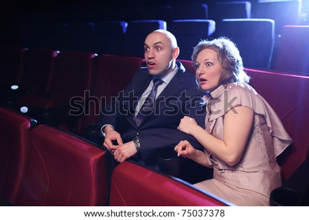 Young adult couple in cinema movie theater scared while watching horror film. - stock photo