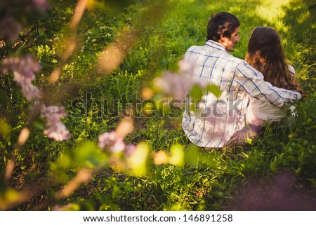 young adult couple in love sitting and hugging at summer park, back view - stock photo