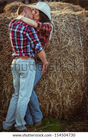 young adult couple kissing near hay - stock photo