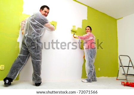 Young adult couple painting interior wall of house