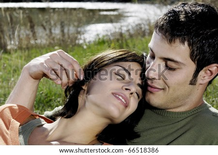 Young adult couple relaxing near a lake