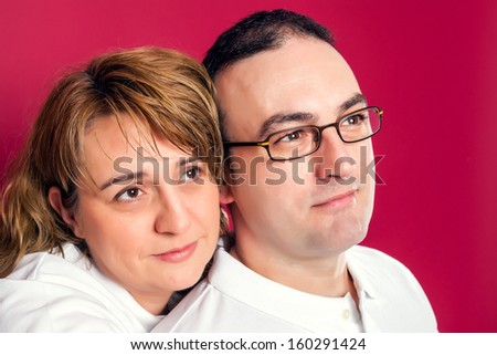Young Adult Couple Smiling Isolated over a Red Background