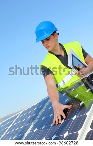 Young adult doing professional training on solar panels plant - stock photo