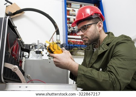 young adult electrician builder engineer worker in front of fuse switch board - focus on hand