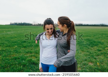 Young Adult Female Runners Arms Around each other smiling in country field - stock photo