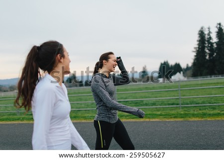 Young Adult Female Runners walking on country road smiling