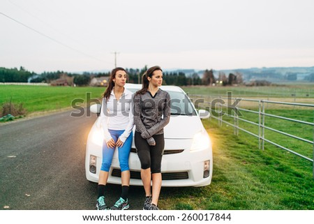 Young Adult Females resting on car after run in country - stock photo